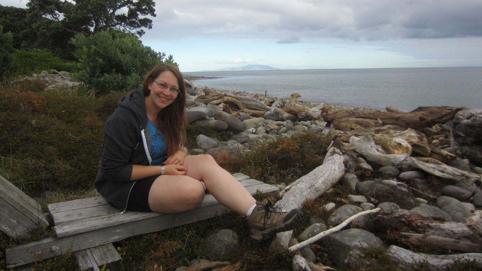 Katie sits on a bench on a rocky beach with the ocean and trees in the background