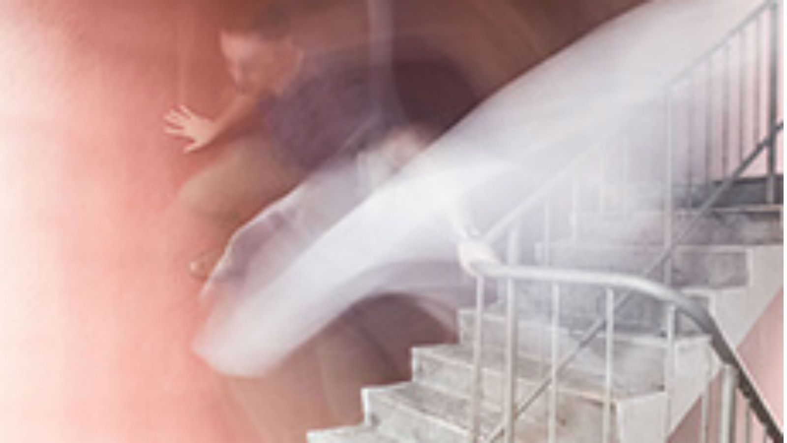 An motion blurred image of someone coming down stairs.