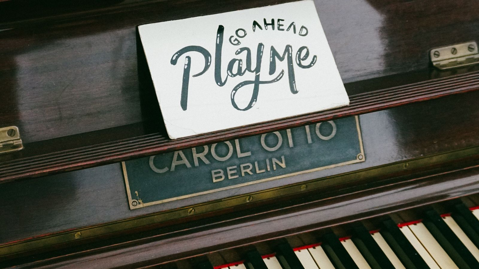 piano displaying a sign saying play me