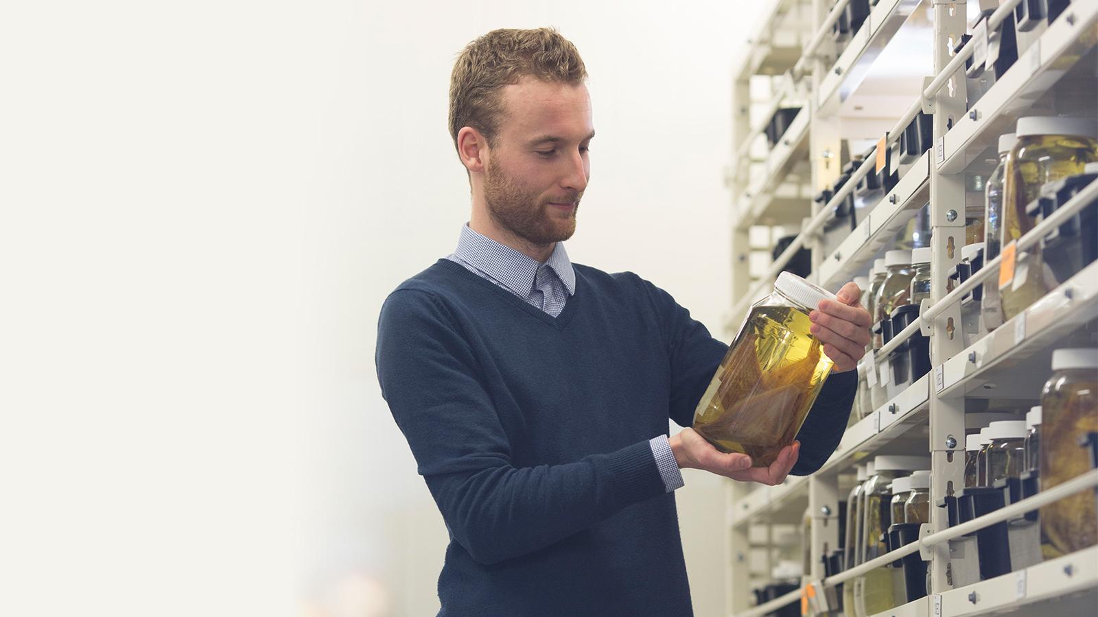Postgraduate student looking at a specimen jar in the Victoria University Coastal Ecology Lab