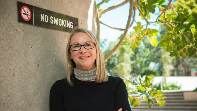 Uta Waterhouse stands in front of No Smoking sign