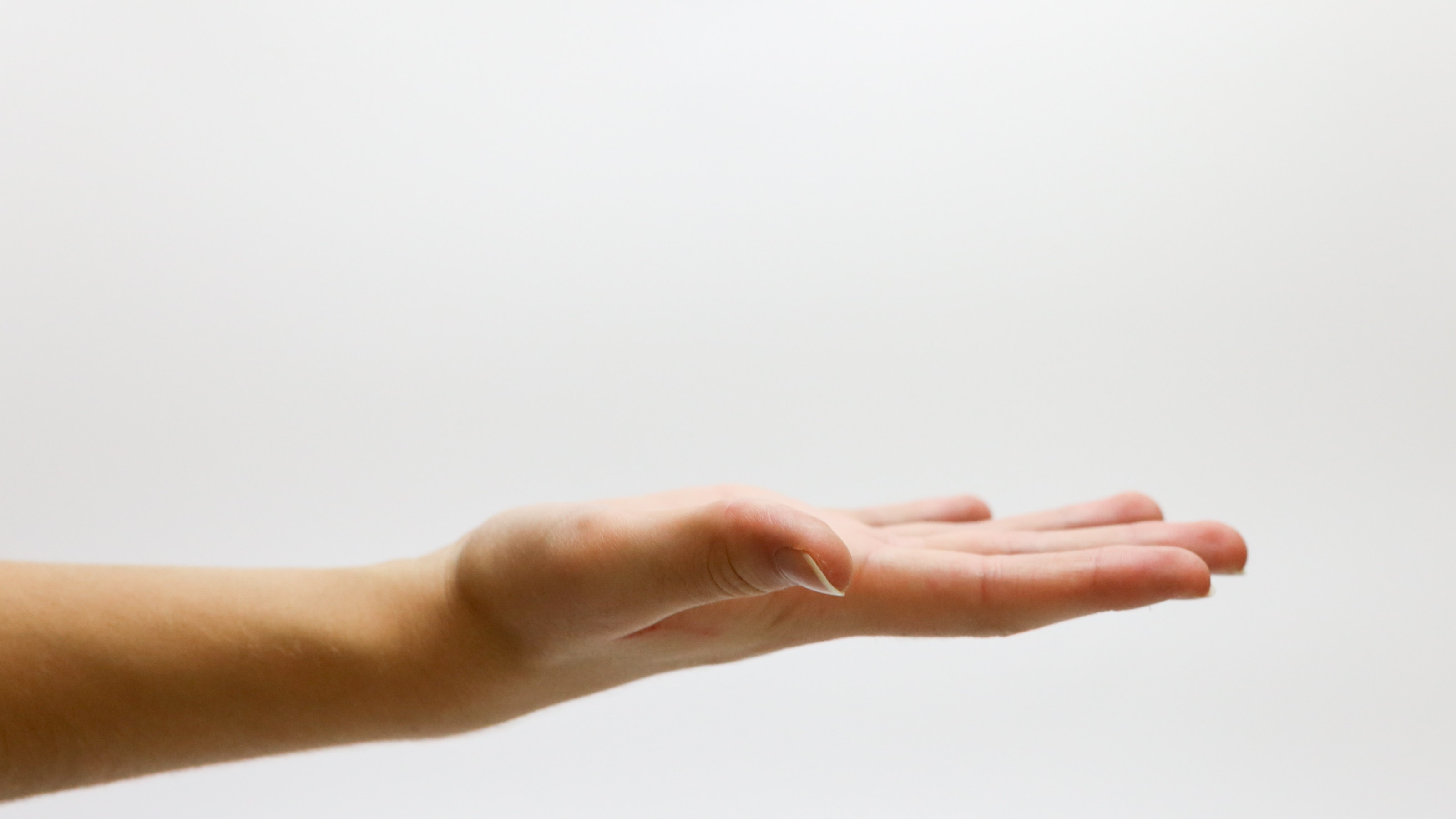 Close up of hand reaching out with a white background.