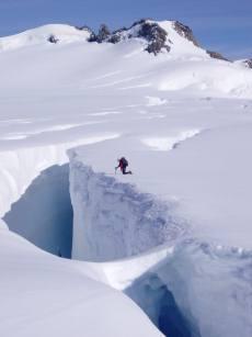 Measuring snow depth down cravsses, Franz Josef Glacier