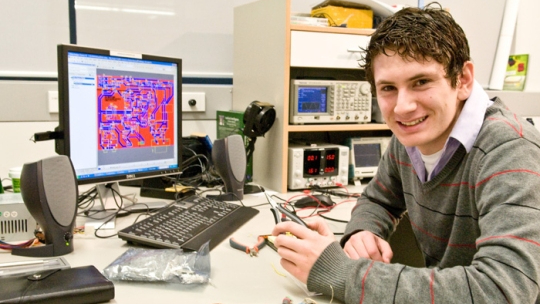 Brendan Vercoelen sits at a desk with a computer and smiles.