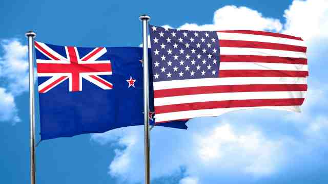 American and New Zealand flags fly in a blue sky