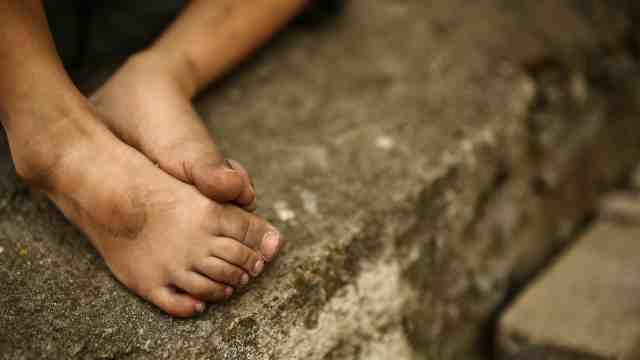 A child's dirty bare feet resting on a concrete step