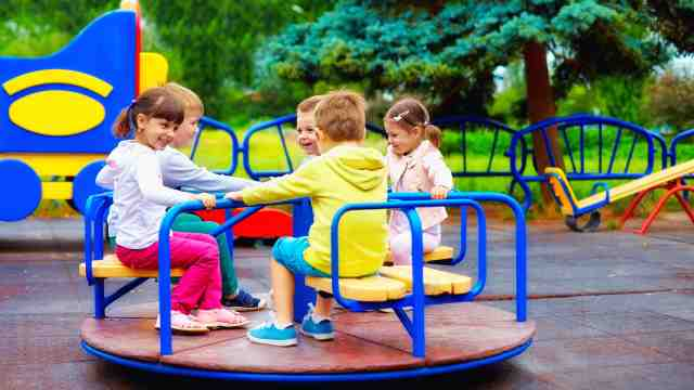 Children playing on a roundabout in a playground.